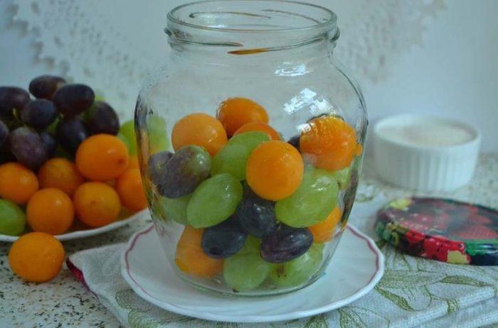 наполняем стеклянную тару алычой и виноградом