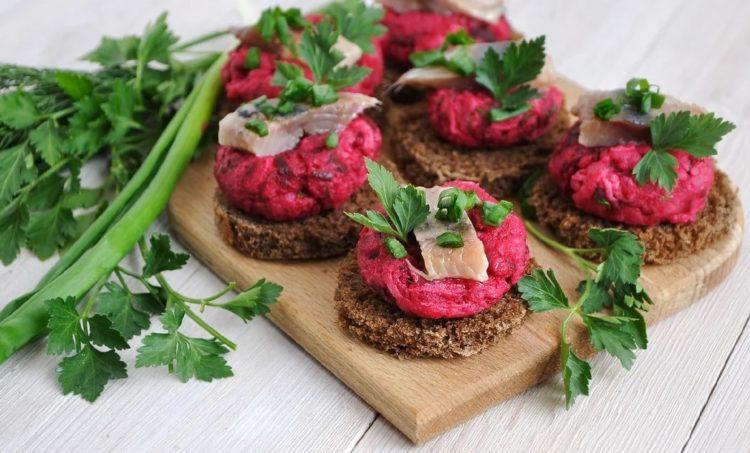 фото закусочных бутербродов с селдкой и свеклой и украшением из свежей зелени