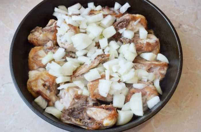 фото лука и куриных бедрышек на сковороде перед началом тушения