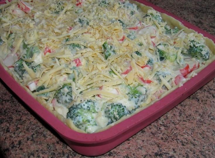 фото подготовленного к выпечке пирога с крабовыми палочками, брокколи и сыром